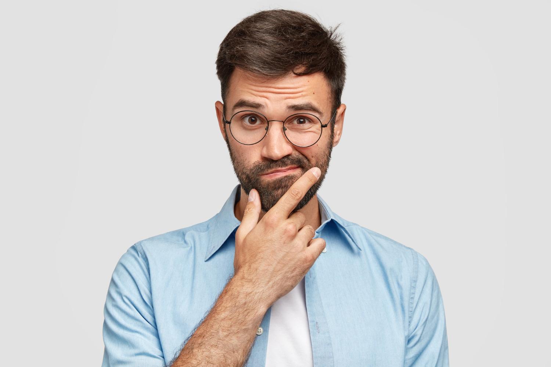 Fotografia de homem branco de barba e óculos, segurando o queixo com expressão de dúvida.