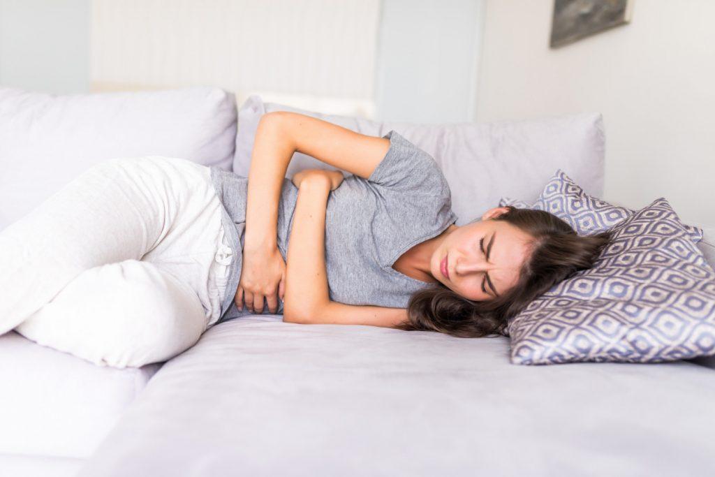 Fotografia de uma mulher jovem deitada no sofá, segurando o abdômen com dor.