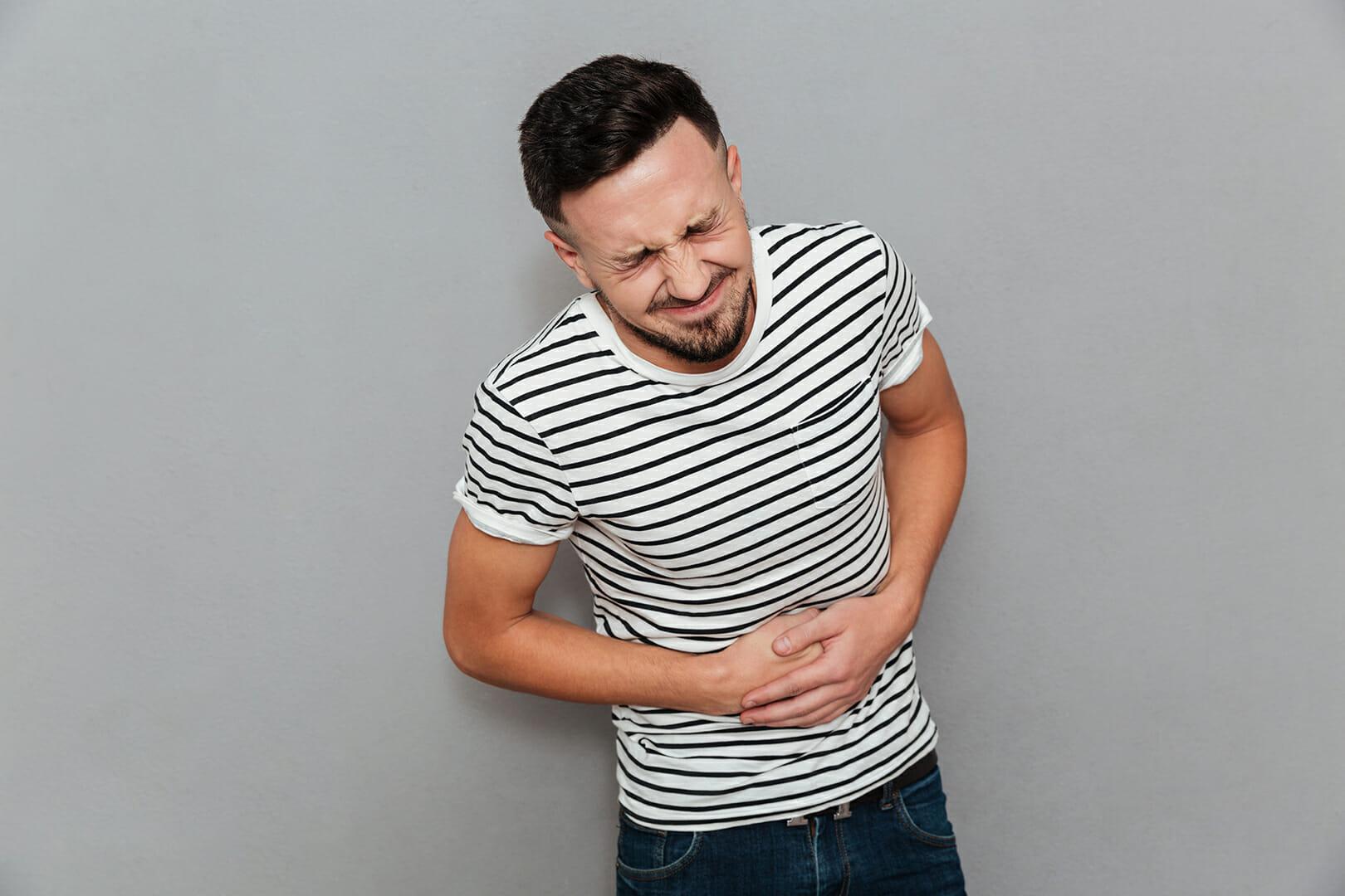 Fotografia colorida de homem jovem com dor na região da barriga. Sua expressão facial é de dor.