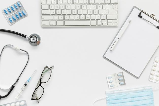Foto colorida de uma mesa de médico vista de cima. Computador, prancheta, estetoscópio, óculos, seringa, máscara e cartelas de comprimidos.