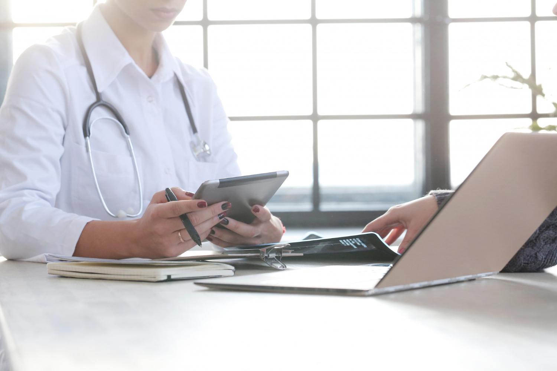 Fotografia colorida de médica com tablet na mão, em frente a um computador e um paciente. Ela está de frente para um paciente.