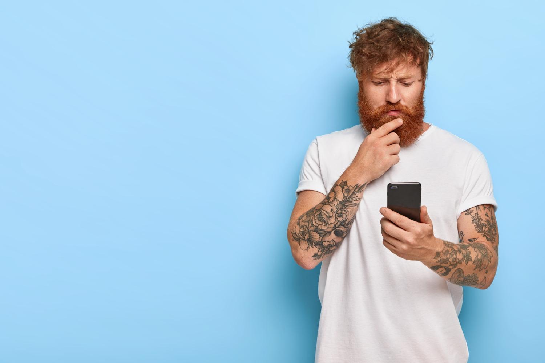 Fotografia colorida de homem ruivo e com barba, com mão no queixo, com dúvida a respeito do que vê na tela do celular (em sua mão). Como é a consulta com a coloproctologista?