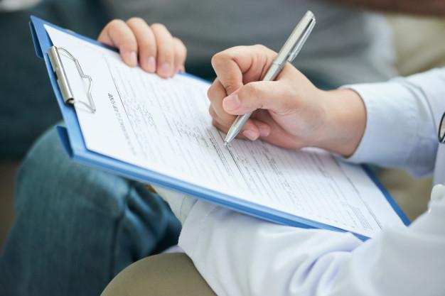 Fotografia colorida de uma médica anotando em uma prancheta. Um paciente está na sua frente.