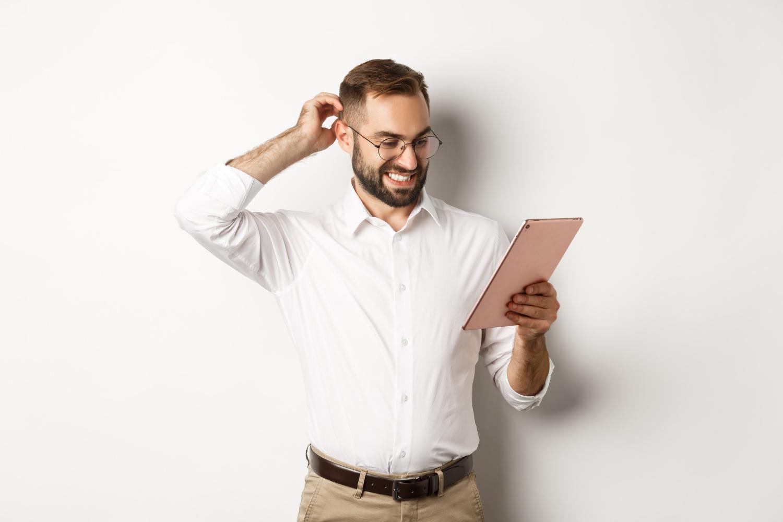 Fotografia colorida de homem bonito com roupa social olhando para um tablet enquanto coça a cabeça, com dúvida.