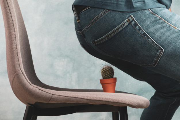 Fotografia colorida de uma pessoa sentando em uma cadeira, onde há um pequeno cacto em um jarrinho laranja. É uma alusão ao incômodo da hemorroida.