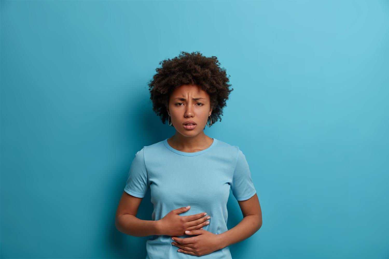 Mulher com camiseta azul claro em fundo azul. Ela tem uma expressão de dor e segura a barriga com as mãos.