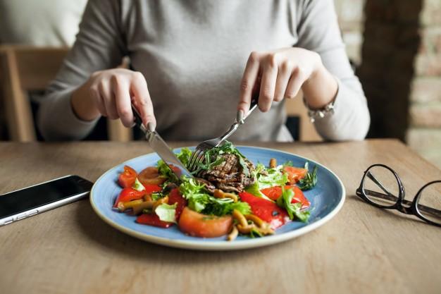 Fotografia de uma mulher comendo um belo prato de comida saudável com diversos legumes e hortaliças.